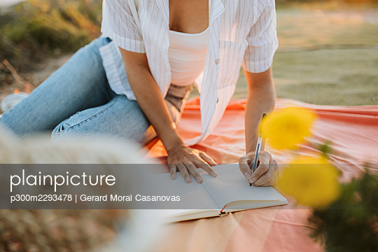Woman writing in book while sitting on picnic blanket - p300m2293478 by Gerard Moral Casanovas