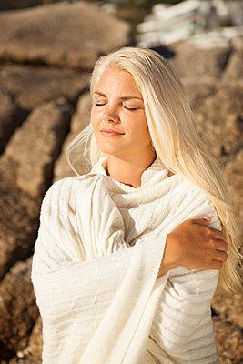 Frau wärmt sich am Strand in Sonne auf - p045m1446176 von Jasmin Sander