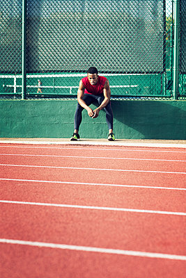 Tired sportsman sitting on retaining wall at field - p1166m1088134f by John Trice