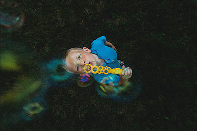 Overhead view of boy blowing bubbles on grassy field - p1166m1204346 by Cavan Images