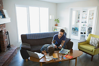 Father helping son with homework in living room - p1192m1019831f by Hero Images