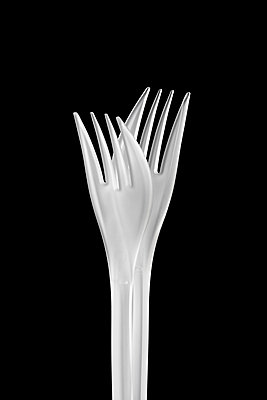 Two white plastic forks against a black background - p1302m1591696 by Richard Nixon