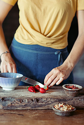 Woman preparing cutting strawberries on cutting board - p300m2005708 von Alberto Bogo