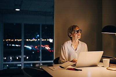 Thoughtful businesswoman sitting with laptop at illuminated desk in creative office - p426m2194901 by Maskot