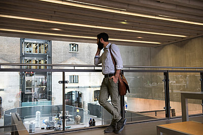 Man on mezzanine in office building making telephone call on smartphone - p429m1513877 by G. Mazzarini