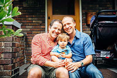 Gay fathers holding baby son on front stoop - p555m1311447 by Inti St Clair