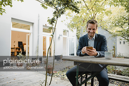 Smiling businessman sitting on bench in green backyard, using smartphone - p300m2202686 by Gustafsson
