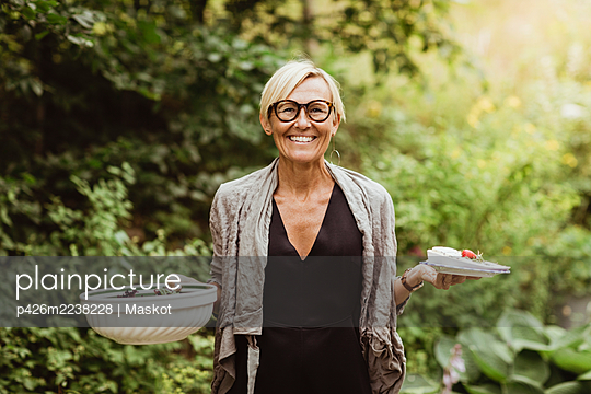 Smiling mature woman holding food in bowl and plate against plants in front yard - p426m2238228 by Maskot