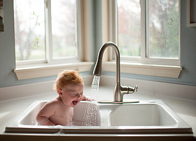 Cute shirtless baby boy sitting in kitchen sink against window at home - p1166m1512514 by Cavan Images