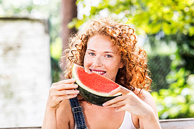 Portrait of redheaded young woman with watermelon - p300m2029067 by Jo Kirchherr