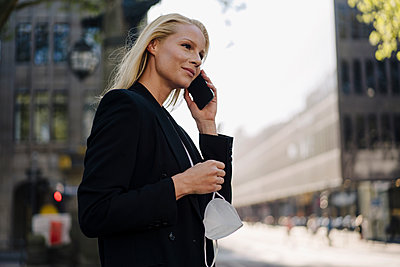 Beautiful businesswoman looking away while talking on mobile phone in city during coronavirus pandemic - p300m2214096 by Joseffson