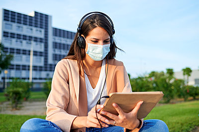 Young woman using digital tablet wearing protective face mask listening music while sitting in public park - p300m2226787 by Kiko Jimenez