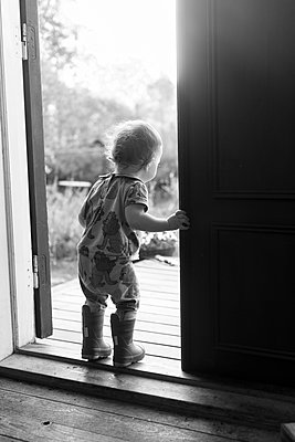 Toddler girl standing at door step - p312m2080385 by Anne Dillner