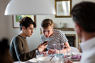 Friend showing phone to teenage boy while sitting at dinner party - p426m1212751 by Maskot