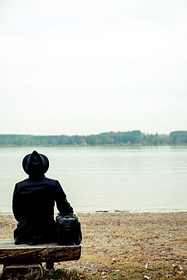 Man with hat sitting on bench on the waterfront - p750m1497086 by Silveri
