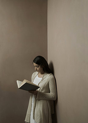 Woman reading book in corner of room - p92412068 by Tacit