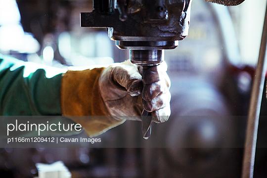 Cropped image of worker adjusting drill in workshop - p1166m1209412 by Cavan Images
