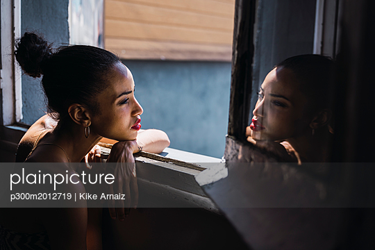 Beautiful young woman leaning on window frame reflected in mirror - p300m2012719 von Kike Arnaiz