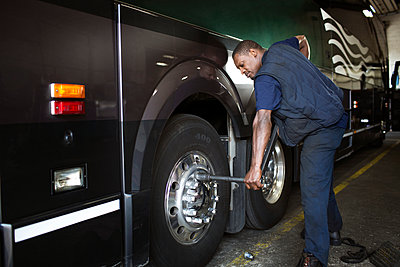 Mechanic fixing bus tire in workshop - p1166m995296f by Cavan Images