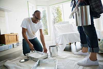Couple preparing to paint living room - p1192m1019818f by Hero Images