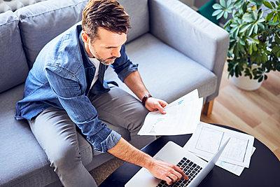 Man with documents sitting on sofa using laptop - p300m1567753 by Bartek Szewczyk