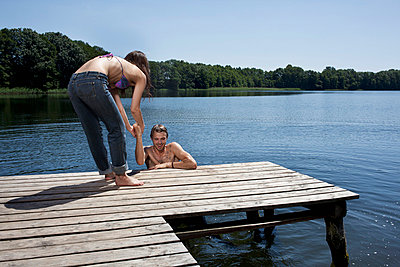 Fun as woman helps man out of the water on jetty - p30119572f by Carl Smith