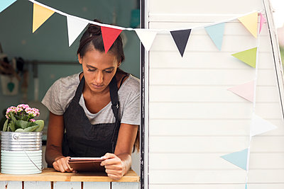 Female owner using digital tablet in food truck - p426m1407066 by Maskot