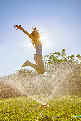 Caucasian girl jumping over backyard sprinkler - p555m1303572 by Chris Clor