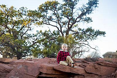 Boy sitting on rock - p756m1584533 by Bénédicte Lassalle