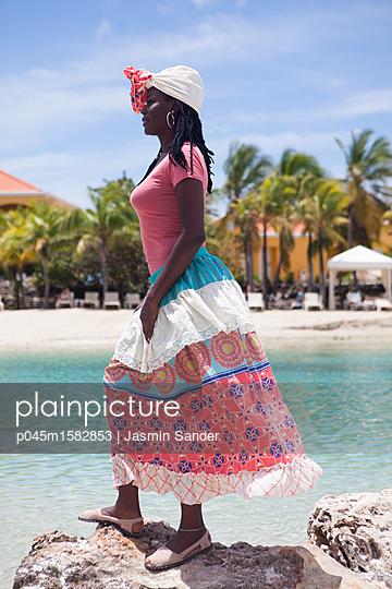 Afroamerikanerin steht am Meer auf Felsen - p045m1582853 von Jasmin Sander
