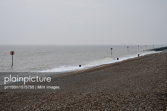 View along shingle beach with a row of partially submerged metal marker poles in the ocean. - p1100m1575755 by Mint Images