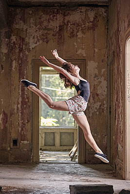 Side view of young woman leaping while practicing ballet in old building - p1166m2024692 by Cavan Images
