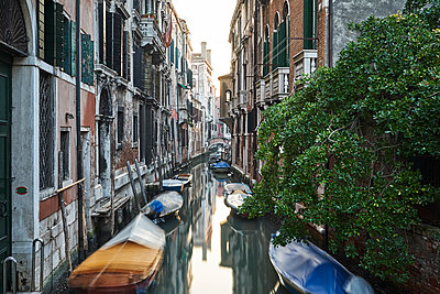 Reflections of boats in a Venetian canal - p1312m1575228 by Axel Killian