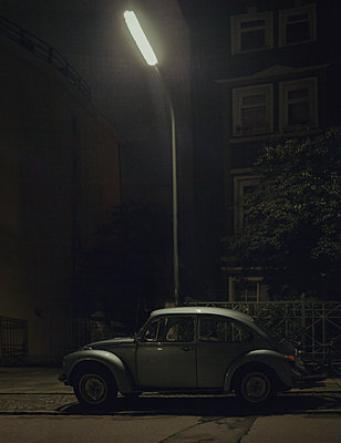 VW beetle parked under street lamp - p1324m1441369 by Michael Hopf