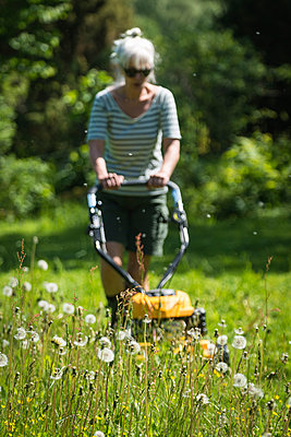 Woman mowing the lawn - p1418m2008109 by Jan Håkan Dahlström
