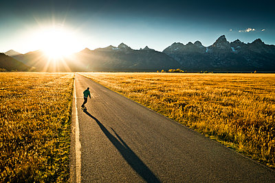 A skateboarder riding towards the sunset in Wyoming. - p1424m1500834 by Rob Hammer