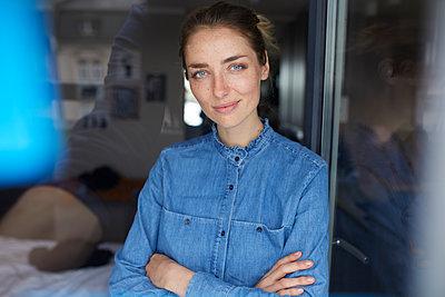 Portrait of smiling woman wearing denim shirt leaning against opened window - p300m1581208 von Philipp Nemenz