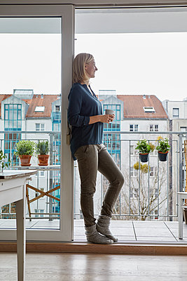 Smiling woman holding cup of coffee looking out of balcony door - p300m2004747 von Rainer Berg