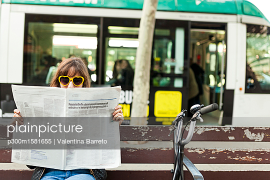 Woman wearing funny sunglasses reading newspaper on bench in the city - p300m1581655 von Valentina Barreto