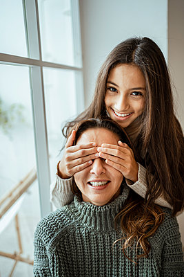 Happy daughter covering eyes of mother while sitting by window at home - p300m2257165 by Rafa Cortés