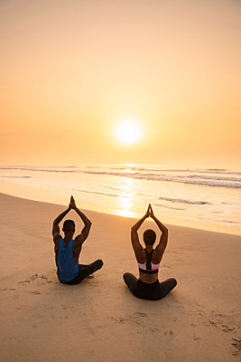 Couple practising yoga on beach - p429m2091580 by Ben Pipe Photography