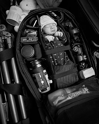 Caucasian infant packed into camera bag - p555m1412053 by Christopher Winton-Stahle