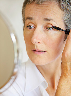 Woman Looking in Mirror Applying Mascara - p669m806296 by Jutta Klee photography