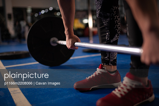 Cropped female athlete deadlifting barbell in gym - p1166m2208066 by Cavan Images