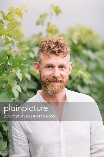 Portrait of bearded man in front of grapevine - p300m2131726 by Alberto Bogo