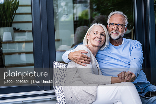 Thoughtful couple holding hands while sitting at balcony - p300m2293821 by Uwe Umstätter