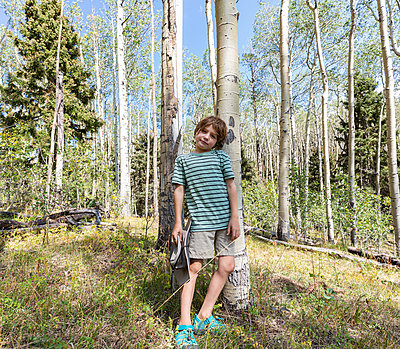 Portrait of 7 year old boy standing in forest of Aspen trees - p1100m2220297 by Mint Images