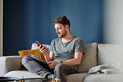 Young man reading short message - p1124m1589439 by Willing-Holtz