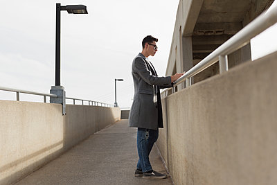 Thoughtful man using mobile phone on bridge - p1315m1565797 by Wavebreak