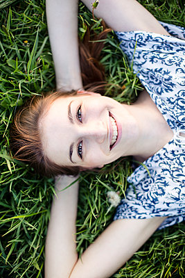 Smiling young woman lying on a meadow enjoying nature - p300m2277259 by Jean Schwarz
